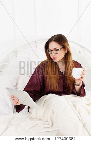 Young woman reads from tablet pc in bed. Girl in eyeglasses looks into gadget tablet pc. Morning coffee. Beautiful woman in nightwear at bed surfing internet at tablet computer. High key.