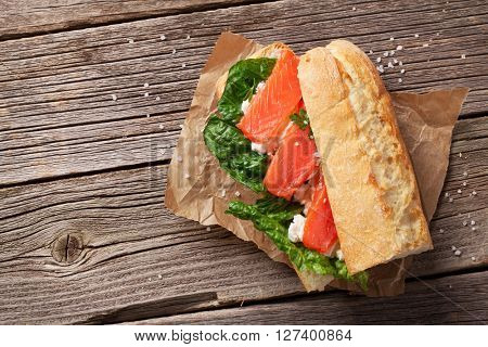 Sandwich with salmon and romaine salad on wooden background. Top view with copy space