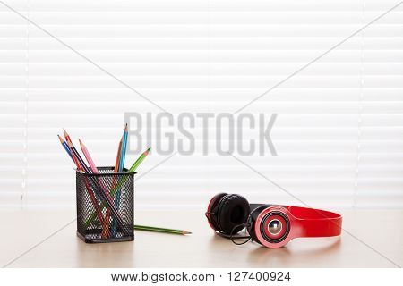 Office workplace with headphones and pencils on wood desk table in front of window with blinds