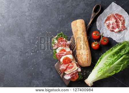 Ciabatta sandwich with romaine salad, prosciutto and mozzarella cheese on stone table. Top view with copy space