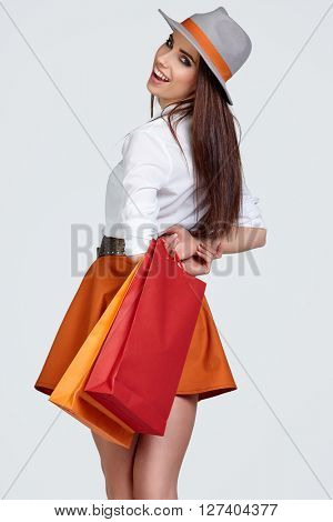 shopping woman holding bags, looking behind. sensual female model smiling. Spring hat.