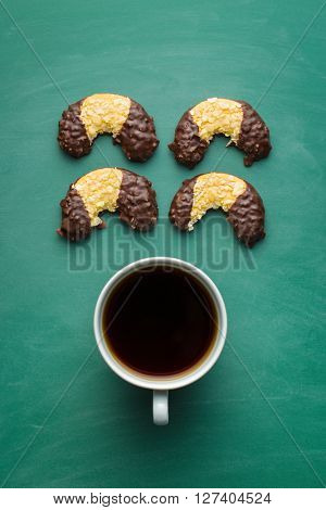 Sweet dessert. Biscuits with chocolate icing and coffee in mug on green chalkboard.