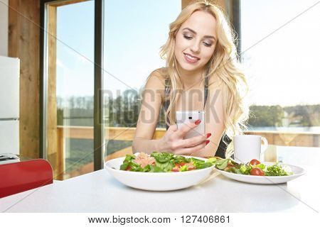 Young sexy women watch her phone and have a breakfast at home in the morning