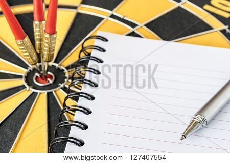 Close up pen on recycle notebook with three darts target on bullseye background Goal target success business investment financial strategy concept abstract background