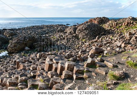 Giants Causeway unique geological formation of rocks and stones on the coast of Antrim County Northern Ireland in sunset light