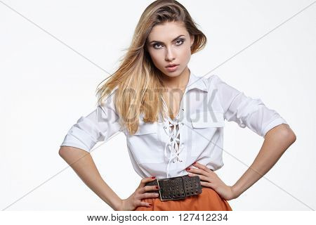 Glamorous beautiful blonde woman in a stylish white top  posing standing facing the camera