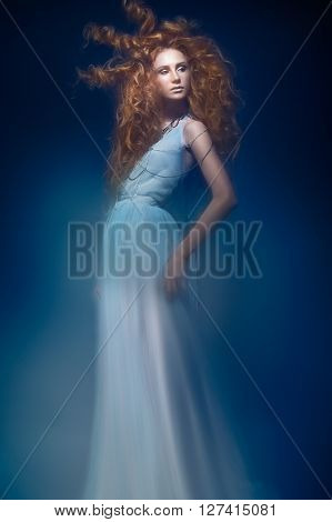 Beautiful fashionable red-haired girl in a transparent dress in mermaid image with creative hairstyle curls. Fashion beauty style. Photos shot in a studio with a mixed light