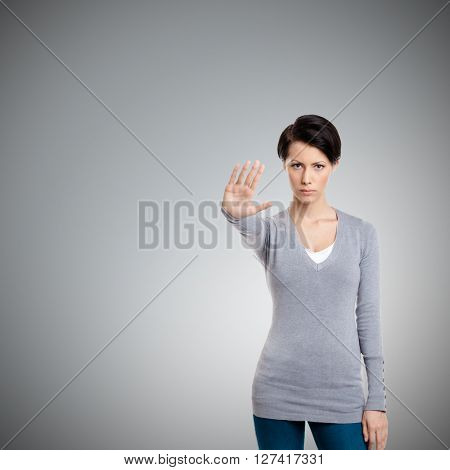 Smart girl shows stop gesture, isolated on grey background