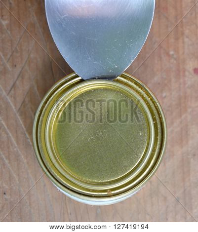 spoon pry can lid on wooden table