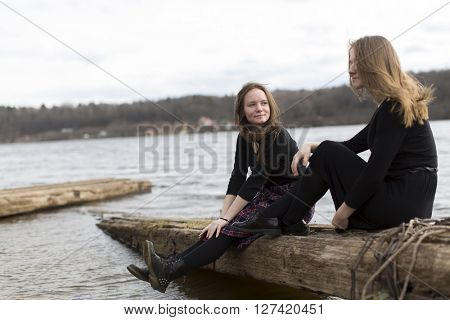 Girls girlfriends sitting together near the river.