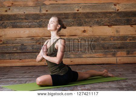 Beautiful woman doing yoga exercises on yoga mat