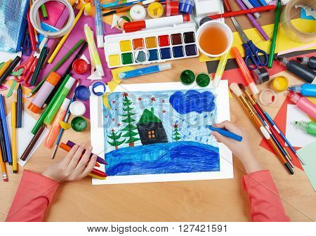 child drawing christmas night in forest with house , top view hands with pencil painting picture on paper, artwork workplace