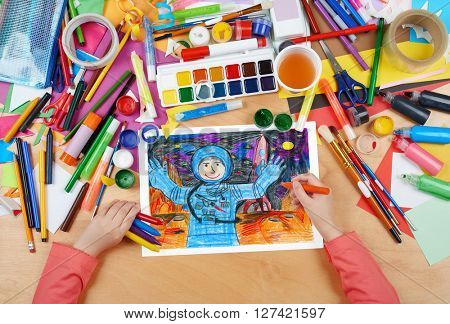 child drawing astronaut exploring the red planet, space concept, top view hands with pencil painting picture on paper, artwork workplace