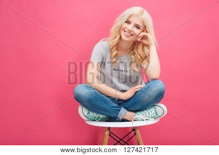 Smiling blonde woman sitting on the chair over pink background