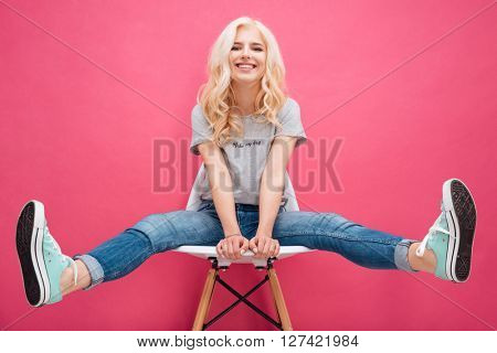 Smiling charming woman sitting on the chair over pink background