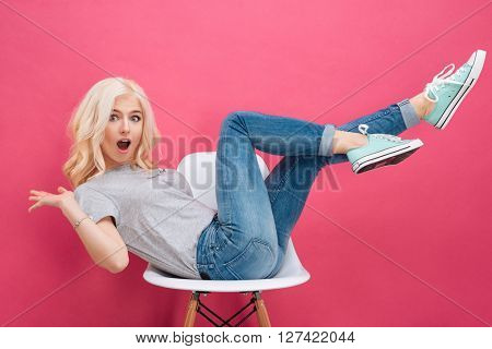 Cheerful woman sitting on the chair with raised legs over pink backgorund