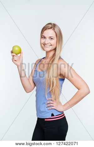 Smiling fitness woman holding apple isolated on a white background