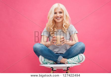 Happy blonde woman holding glass with cappuccino over pink background