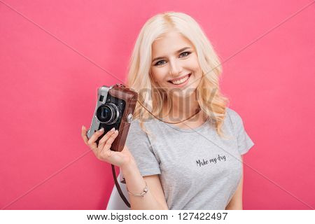Smiling attractive woman holding photo camera over pink background