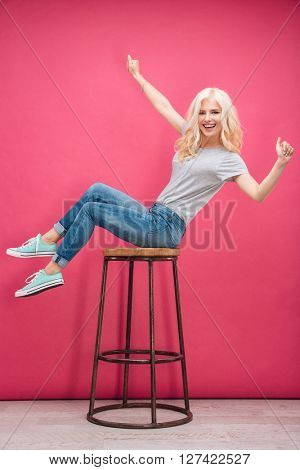 Cheerful funny woman sitting on the chair over pink background and looking at camera
