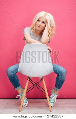 Portrait of a charming woman sitting on the chair and looking at camera over pink background