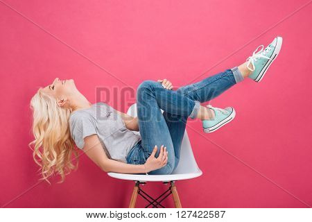 Attractive woman having fun on the chair over pink background