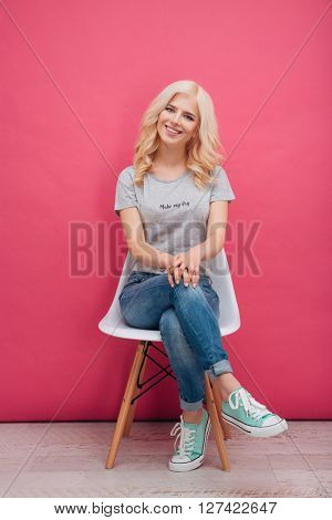 Smiling pretty woman sitting on the chair over pink background