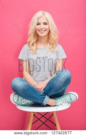 Pretty blonde woman sitting on the chair over pink background