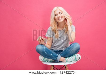 Smiling woman sitting on the chair and listening music in headhpones over pink background