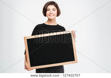 Smiling woman showing blank board isolated on a white background