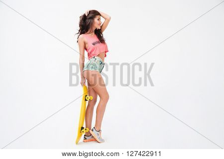 Full length portrait of a sexy woman posing with skateboard isolated on a white background