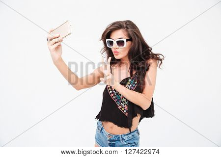 Stylish woman making selfie photo on smartphone and showing peace sign isolated on a white background