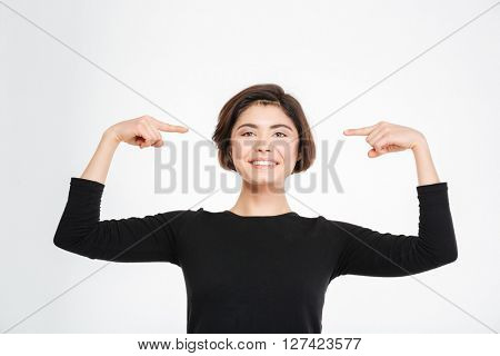 Smiling woman pointing finger at herself isolated on a white background