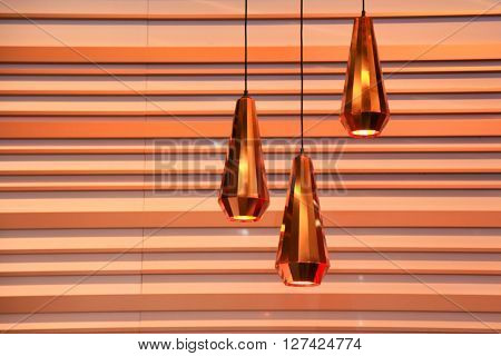 Three modern pendent lamps against striped wall