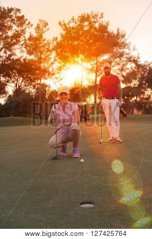 portrait of happy young  couple on golf course with beautiful sunset in background