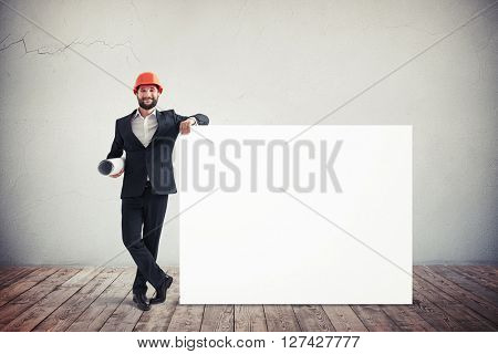 Handsome young architect in red helm near a blank horizontal white banner. Place for text.