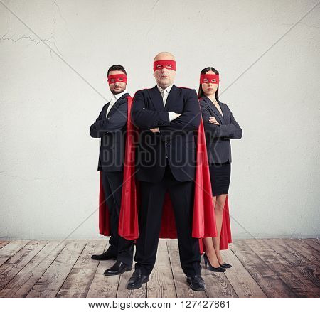 Two businessmen and businesswoman in superhero costume staying side by side with arms folded