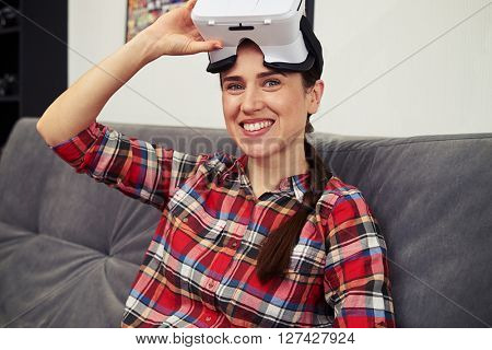Young smiling brunette is sitting on the sofa wearing virtual reality glasses, close up