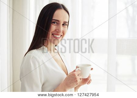 Young smiling pretty woman stands and holding coffee  indoor
