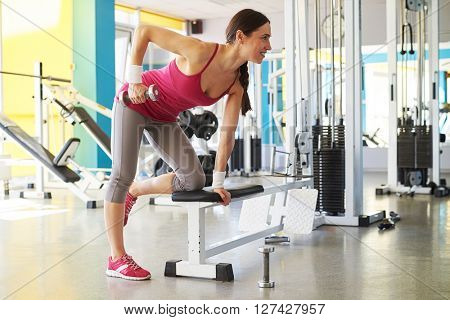 Smiling woman is working with dumbbells kneeling on the seat in the sport club