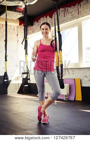 Young girl in sportswear is staying near the trx and holding thumbs up