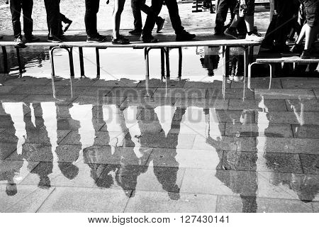 Walking people reflect in a puddle on San Marco square in Venice, Italy. Black and white image