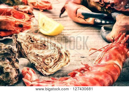 Steamed crab shrimps and fresh oysters on wooden background. Sea food dinner concept