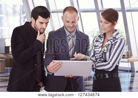 Caucasian business people looking at laptop computer screen at office. Bristly businessmen in suit and businesswoman pointing at screen. Standing.