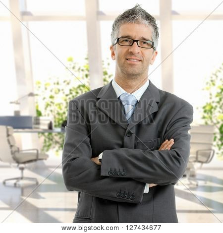Caucasian male mid adult business expert standing arms crossed at office. Wearing suit and glasses.