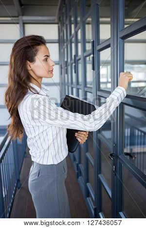 Young businesswoman knocking office door