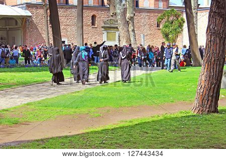 ISTANBUL, TURKEY - MARCH 30, 2013: Muslim veiled woman and tourists in Topkapi palace, Istanbul, Turkey
