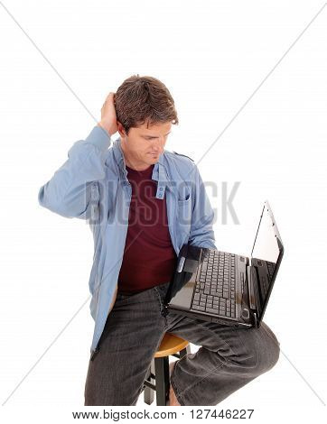 A young man sitting on a chair with his laptop on his lap and is wondering what he see's on the laptop isolated foe white background.