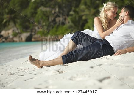 Beautiful Young Couple Kissing On Sunset Lying On Sand, Sunset Time.