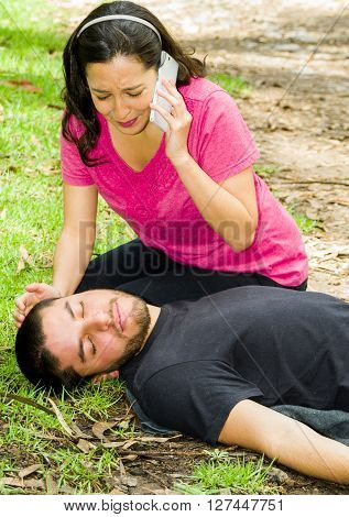 Young man lying down with medical emergency, woman sitting by his side calling for help, outdoors environment.